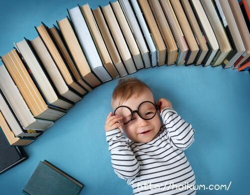 たくさんの本に囲まれてうれしそうな5才の子ども