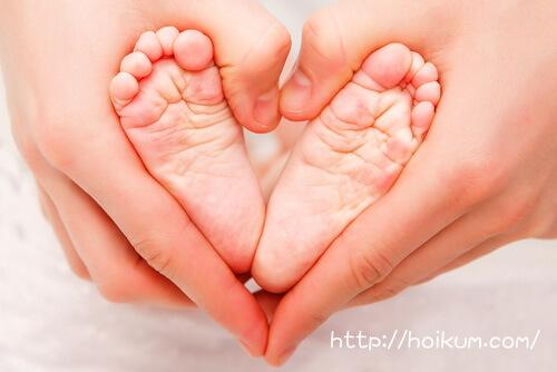 赤ちゃんの足を包む保育士の手