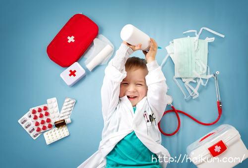 白衣を着た男の子と救急箱