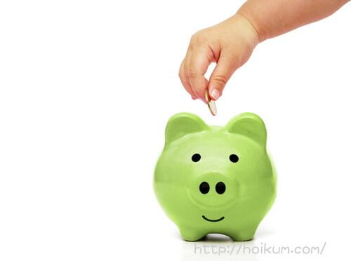 貯金箱にコインを入れる子ども