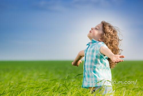 草原で深呼吸する認定こども園の男児