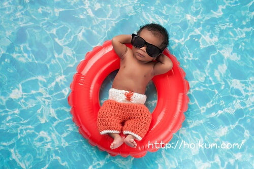 浮き輪でプールで遊ぶ2歳児