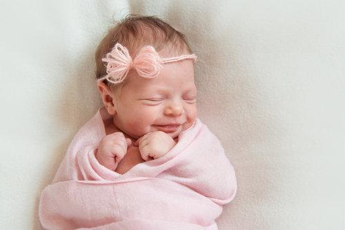 ピンクのおくるみに包まれた赤ちゃん。保育士がしっかり面倒みます